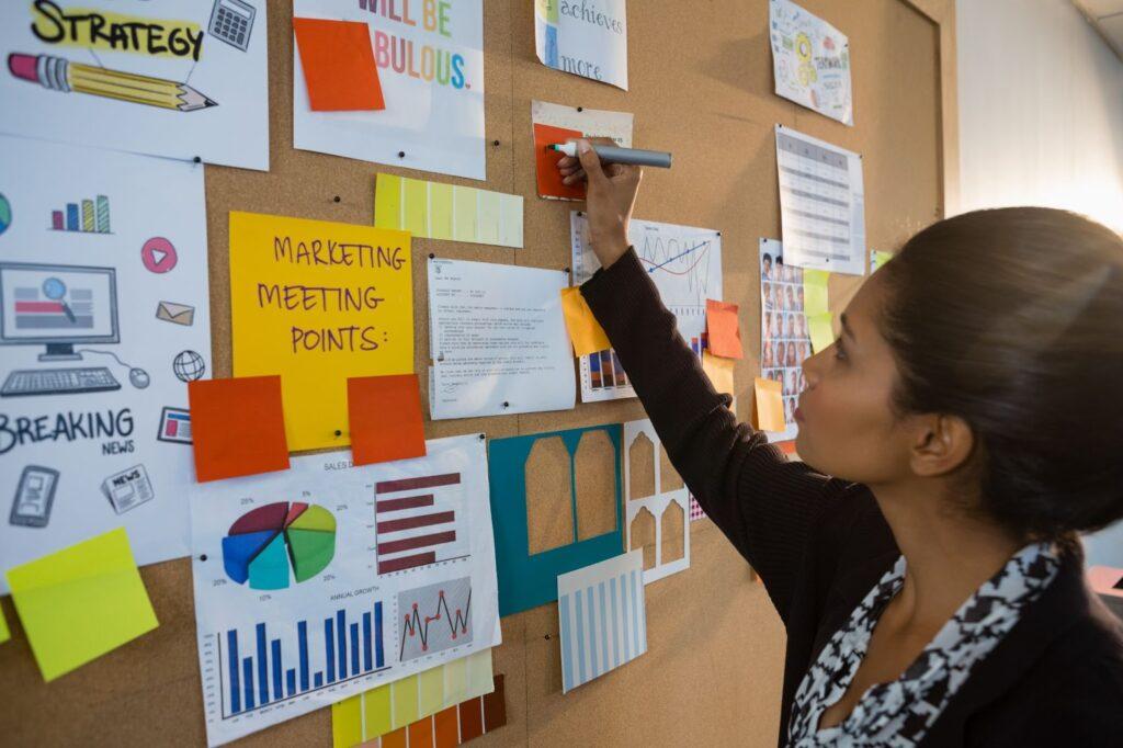 Una mujer publicando algo en un tablero de anuncios.