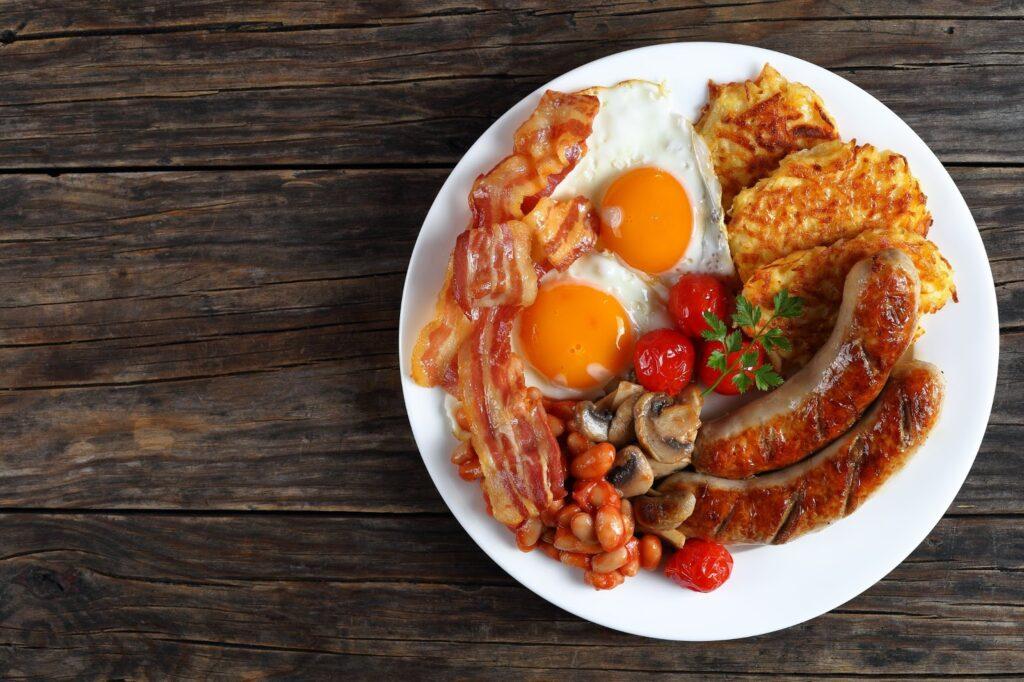 Prato completo com café da manhã tradicional inglês com linguiça, bacon, ovos, feijão, tomate e batatas fritas.