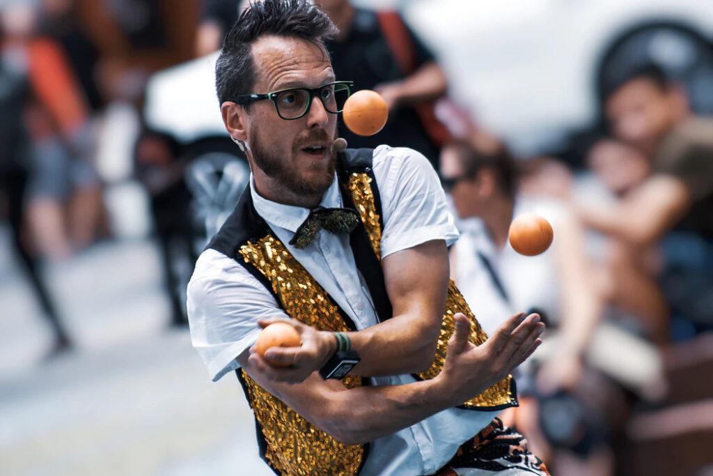 Um artista de rua fazendo malabarismo com três bolas.