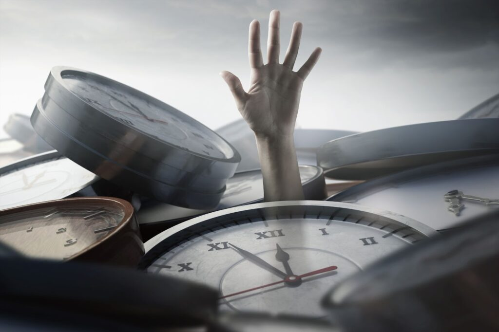 A hand of a person that is buried under different clock faces.