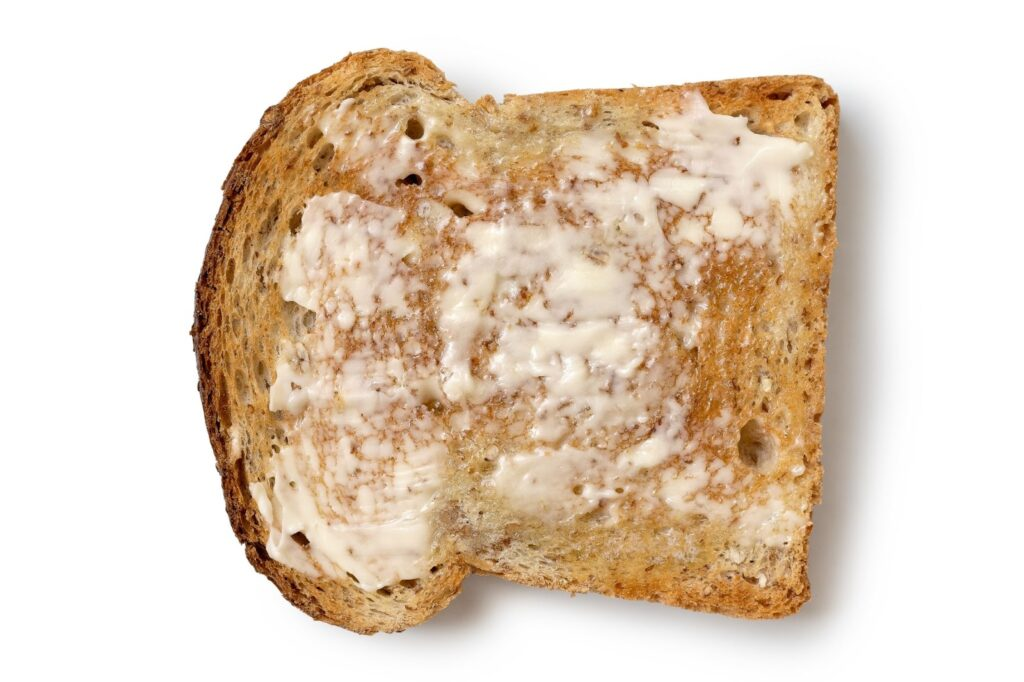 A piece of toast with a thin layer of butter spread on it.